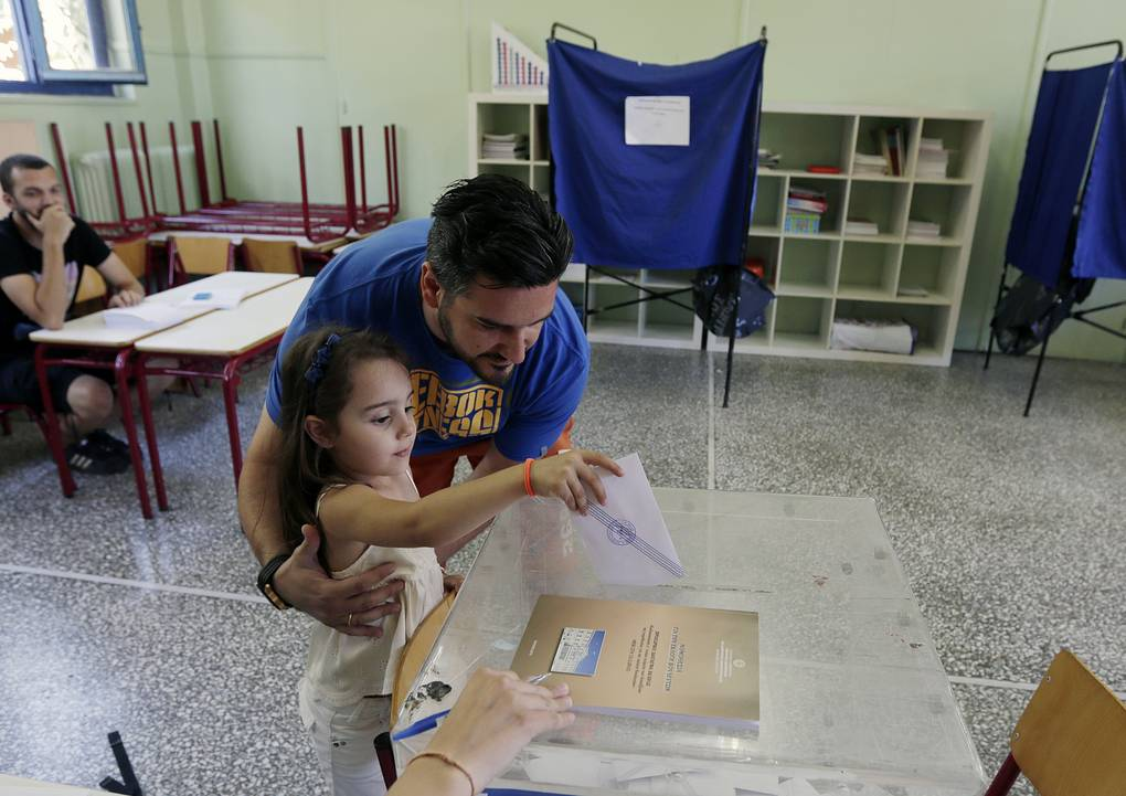 A man let's his daughter cast his vote at a polling station in Athens, Sunday, July 5, 2015. Greeks were voting Sunday in a bailout referendum that will decide the country's future, with opinion polls showing people evenly split on whether to accept creditors' proposals for more austerity in exchange for rescue loans or defiantly reject the deal. (AP Photo/Petr David Josek)