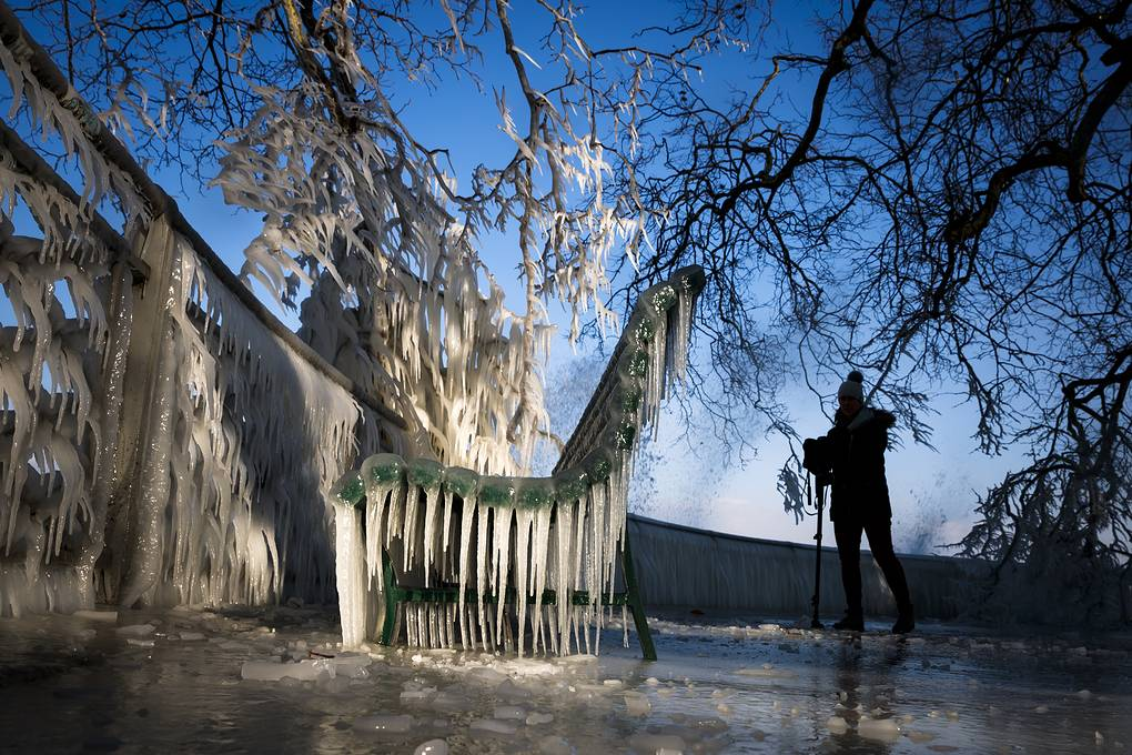 A woman films an ice covered bench on the frozen shore of Lake Geneva during a windy winter day, in Geneva, Switzerland, 26 February 2018. Media reports state that extreme cold weather is forecast to hit many parts of Europe with temperatures plummeting to a possible ten year low. EPA-EFE/VALENTIN FLAURAUD