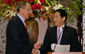 Russia's Foreign Minister Sergei Lavrov (L), shakes hands with his Japanese counterpart Fumio Kishida (R)
