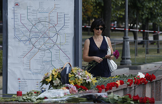 People lay flowers at the entrance to the metro in Moscow