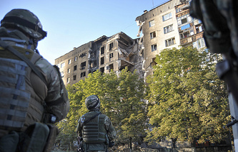 Ukrainian soldiers look at the damage sustained to a building in Lisichansk