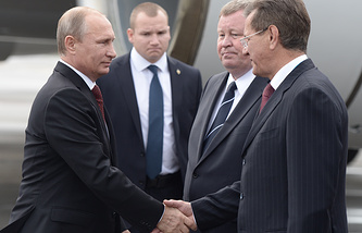 Vladimir Putin (left) and Astrakhan Region governor Alexander Zhilkin (right) shake hands in Astrakhan