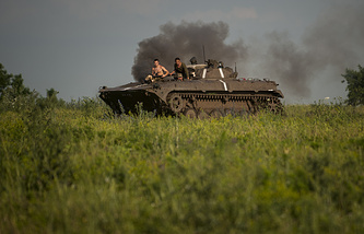 Ukrainian servicemen riding atop an armored vehicle in east Ukraine (archive)