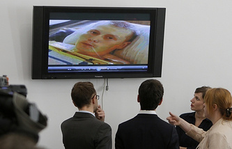 Reporters look at the TV screen showing Alexander Alexandrov
