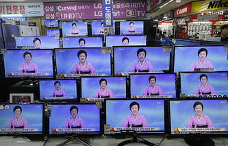 TV screens showing a North Korean newscaster reading a statement from the North's Nuclear Weapons Institute