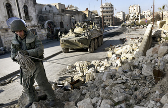 A Russian sapper looks for mines in a street in Aleppo, Syria
