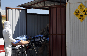 Experts evacuate a victim of a suspected chemical weapons attacks in the Syrian city of Idlib, at a local hospital in Reyhanli, Turkey