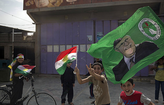 Children holding Kurdish flags run on the streets of the city of Kirkuk