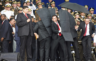 Security personnel surrounding Venezuela's President Nicolas Maduro during an incident as he was giving a speech in Caracas, August 4