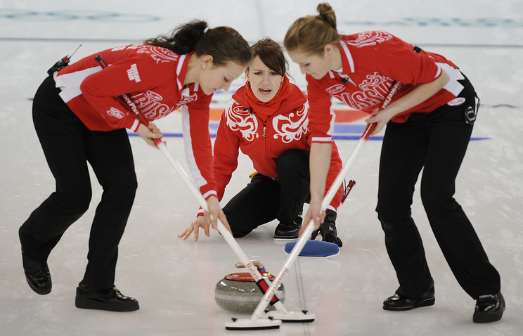 Russia's Yekaterina Galkina (C) shouts to sweepers Anna Sidorova and Margarita Fomina (L-R) in a women's curling match against the U.S. at the Vancouver 2010 Olympics
