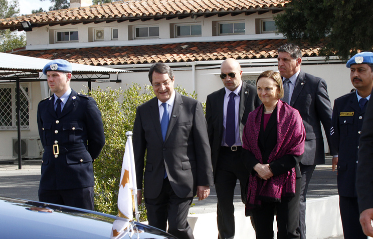 UN Chief of Mission Lisa Buttenheim (R) and Cyprus President Nicos Anastasiades (L) arrive for a meeting with Turkish Cypriot leader Dervis Eroglu at the UN-controlled buffer zone