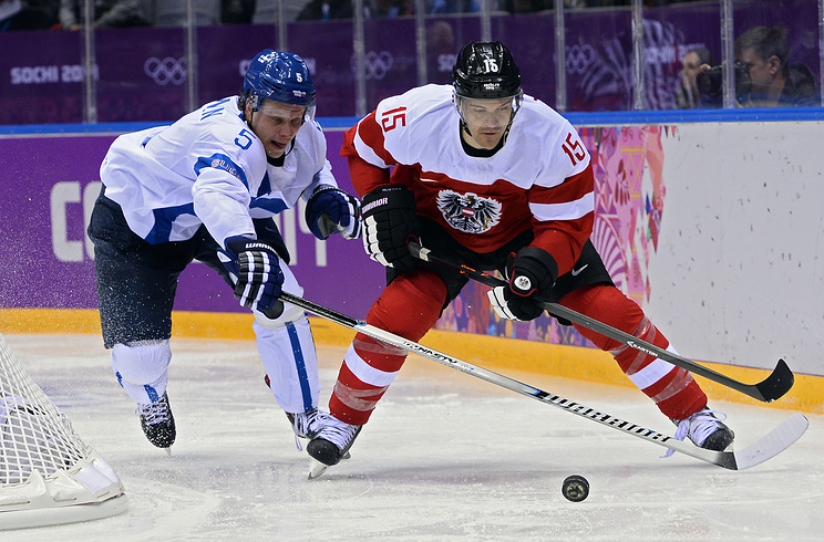 Lasse Kukkonen (L) of Finland fights for the puck with Manuel Latusa (R) of Austria during the match between Finland and Austria