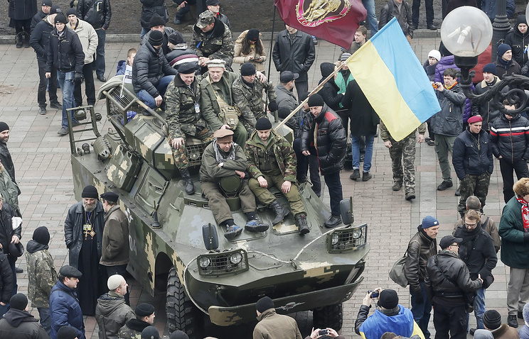 Protesters sit on a military vehicle near the Ukrainian Parliament building in Kiev