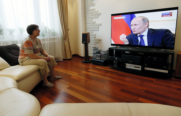 A woman watches TV showing Russian President Vladimir Putin speaking about the situation in Ukraine