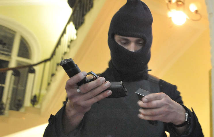 A Ukrainian rebel examines a pistol in the seized regional Interior Ministry department in Lviv on Feb. 19