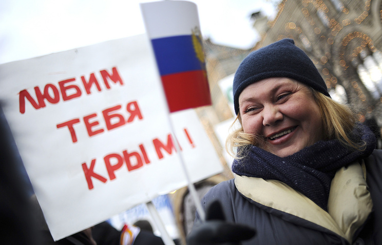 """A rallier with a poster saying: """"Love you, Crimea"""""""