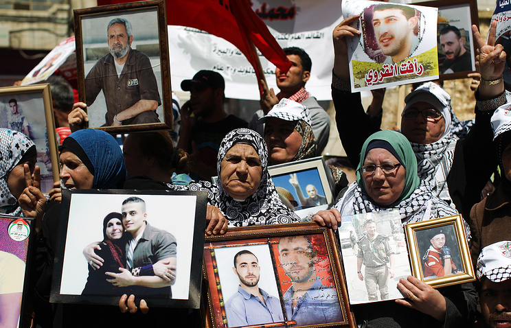 Palestinian family members holding pictures of their relatives jailed in Israeli prisons