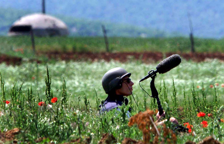 A soundman sits with a bullet proof vest and a helmet in a field efforting to record the sound of shelling in Yugoslavia in 1999 (archive)