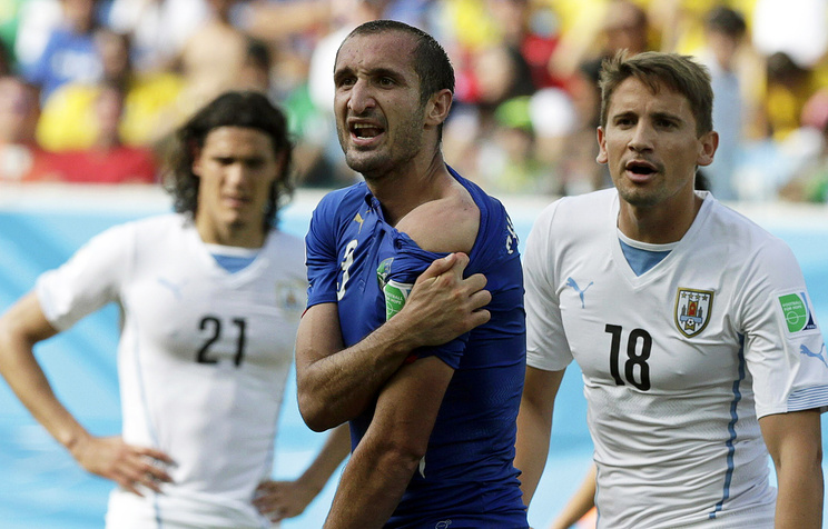 Italy's Giorgio Chiellini (C) shows his shoulder and claims he was bitten during the FIFA World Cup 2014 group D preliminary round match between Italy and Uruguay at the Estadio Arena das Dunas in Natal, Brazil, 24 June 2014