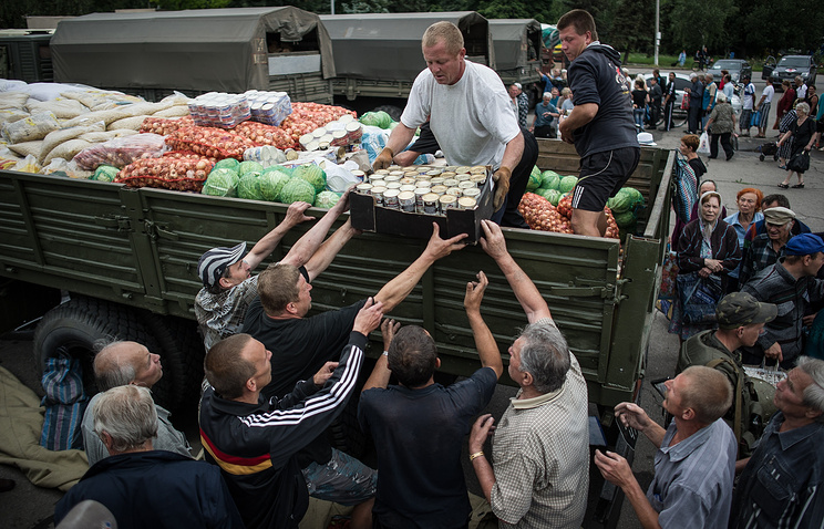Local people unload a truck with humanitarian aid in Sloviansk