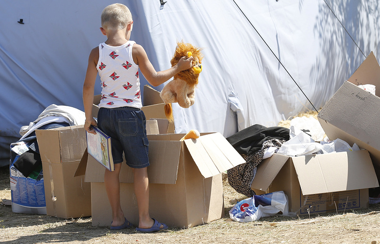A child inspects boxes with humanitarian aid at a refugee camp in Russia's Rostov region