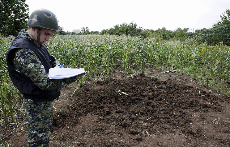 Member of the investigating committee near a shell crater after shelling from Ukrainian territory hit the small Russian city of Donetsk