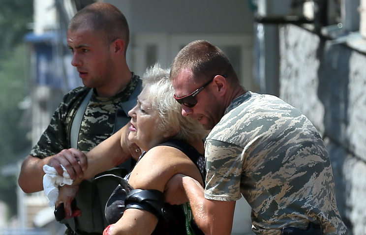 Local men help a wounded woman after a mortar attack by the Ukrainian army on the center of Donetsk, Aug. 14