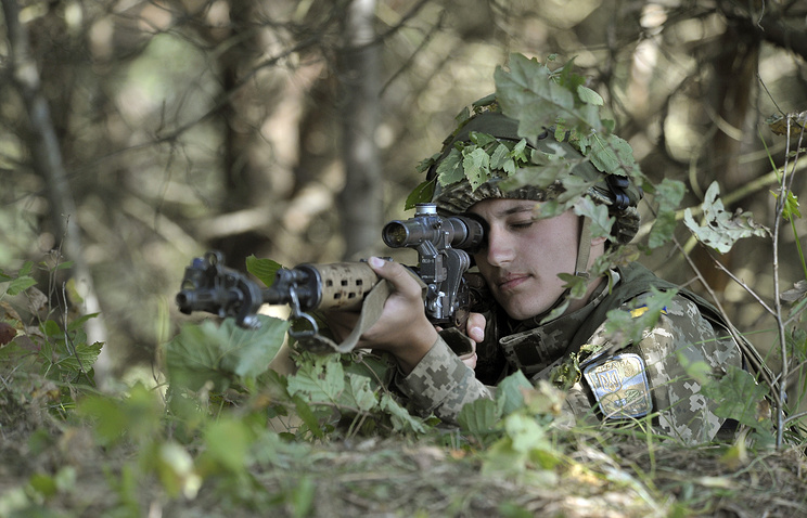 Ukrainian soldier aims his rifle as he takes part in a joint military drills