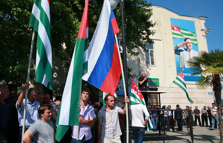 People hold national flags of Russia and Abkhazia in Sukhum