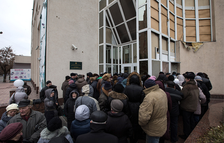 People stand in line to get their pensions in eastern Ukraine's Luhansk