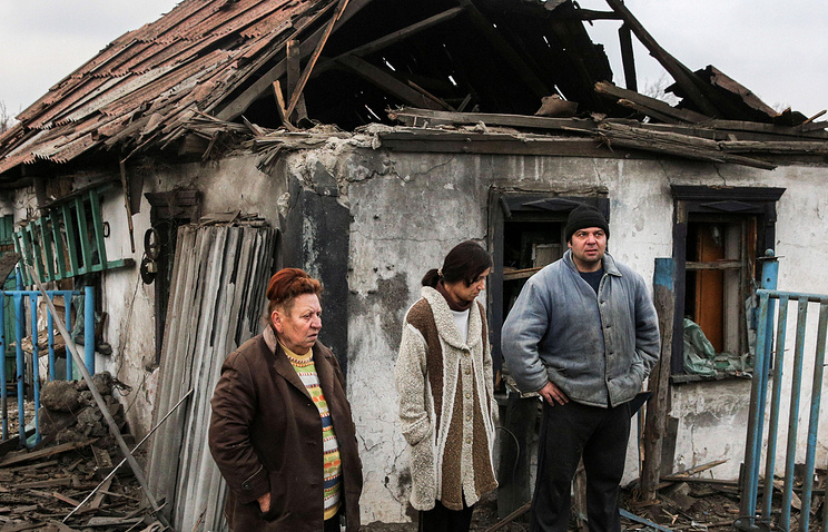 Local residents outside a destroyed house in Donetsk region