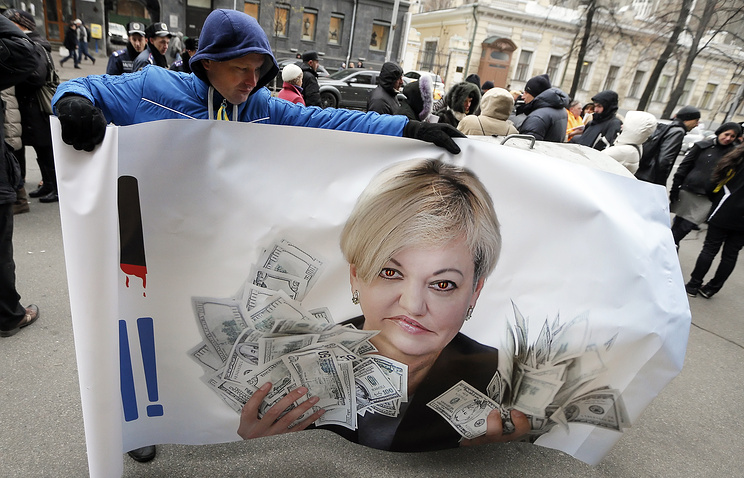 Ukrainian protester with a banner showing the Head of Ukrainian National Bank, Valeria Gontareva, during a rally in front of National Bank building in Kiev
