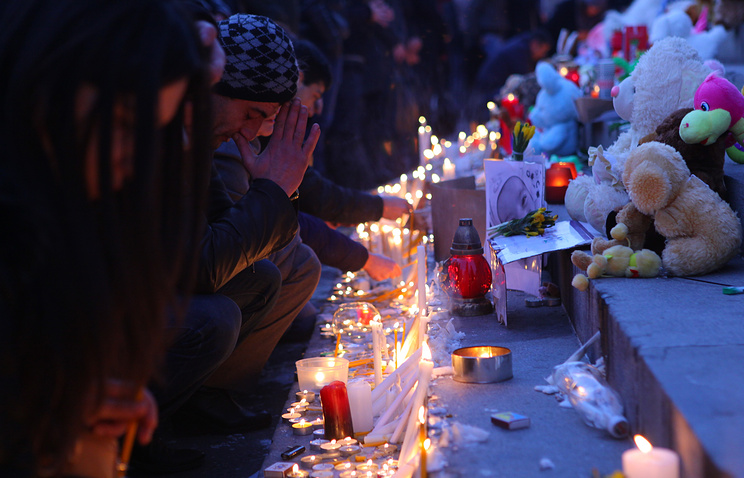 Armenian people light candles in memory of a 6-month-old baby and his family slain in Gyumri