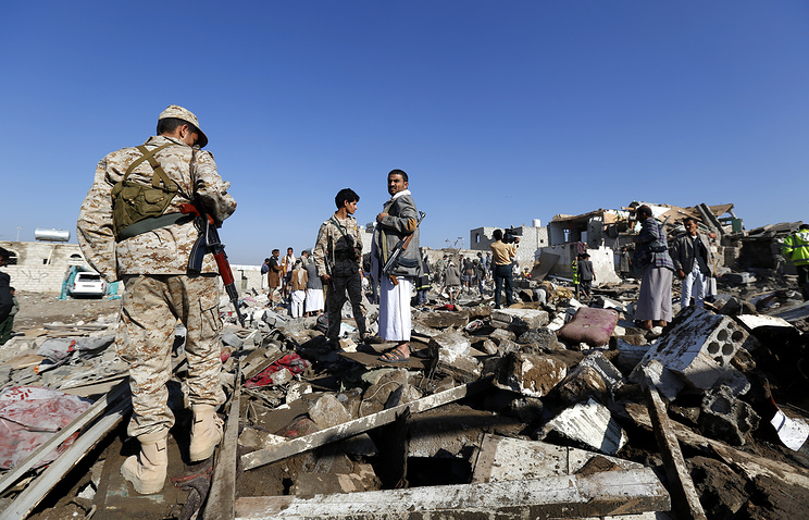 Houthi militia members inspecting houses destroyed by a Saudi air strike, in Sanaa, Yemen
