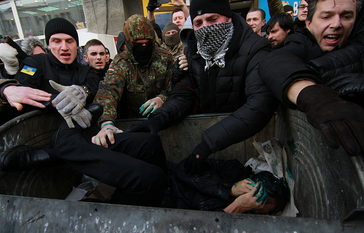 Crowd don't let a politician out of a dumpster in Ukraine's Kharkiv, December 2014