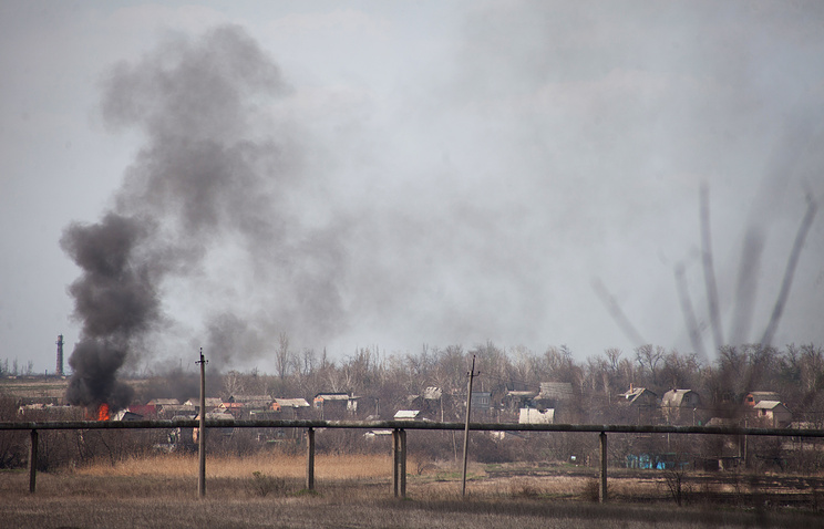 Smoke rises over a village near the Donetsk airport, Apr. 13, 2015