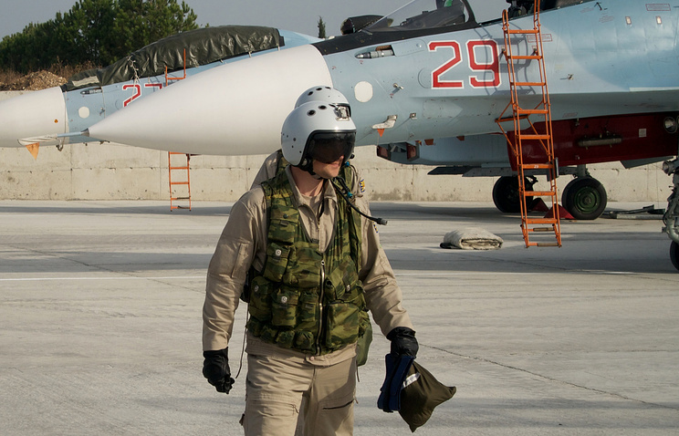 Russian pilot walking from his Su-30 jet in the background at airbase in Syria