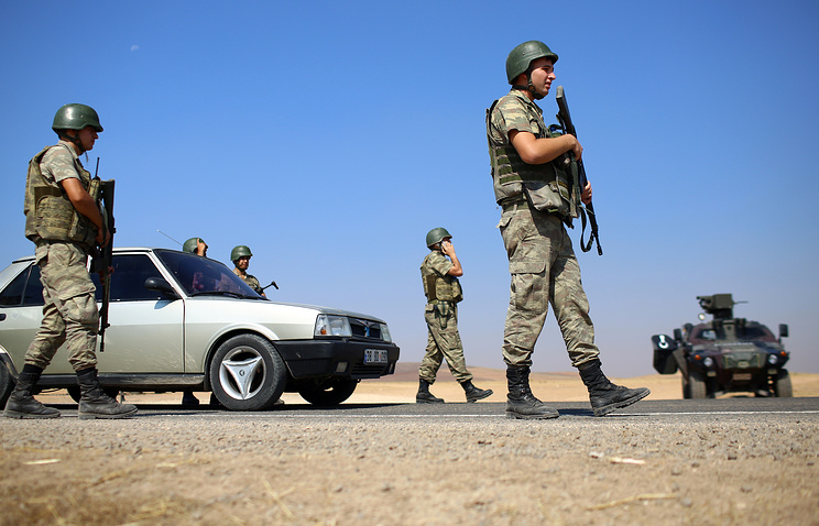 Turkish soldiers take position on a road near Suruc on the border with Syria