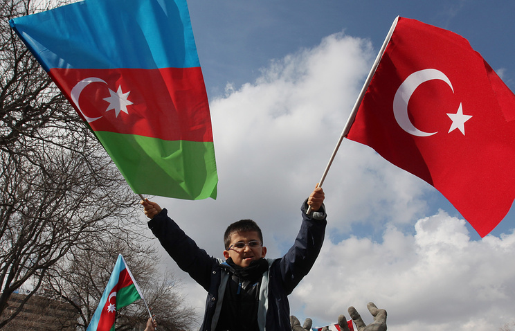 A boy waving Turkish and Azeri flags