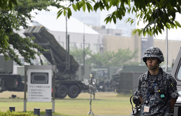Military personnel standing at guard near a Japan's Ground Self-Defense Force Patriot Advanced Capability-3 (PAC-3) missile interceptor unit deployed to counter North Korea's launch of ballistic missile