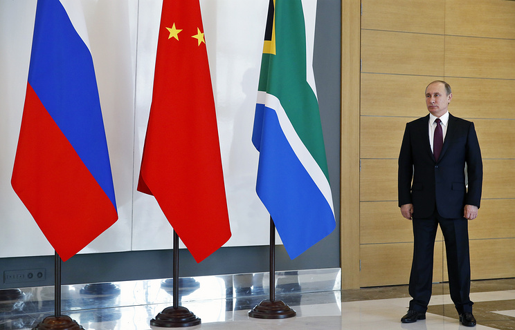 Russian President Vladimir Putin standing next to national flags of Russia, China and South Africa - three of the five BRICS countries (archive)