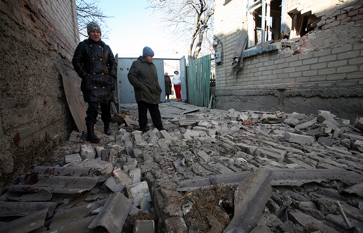 Local residents seen by a house damaged in a shelling attack in Donetsk region
