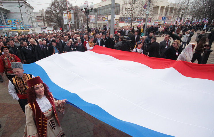 People carry a large Crimean flag during a celebration marking the 3rd anniversary of the 2014 referendum on the political status of Crimea and Sevastopol