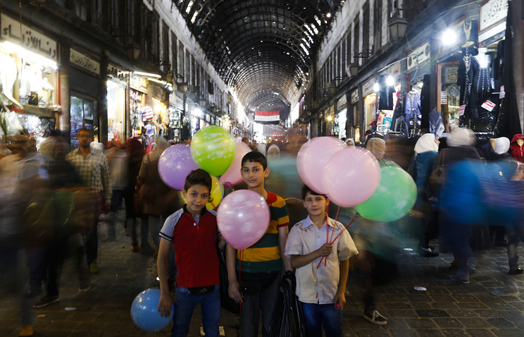 Syrian boys sell balloons at the Hamadiyah market in the Old City of Damascus