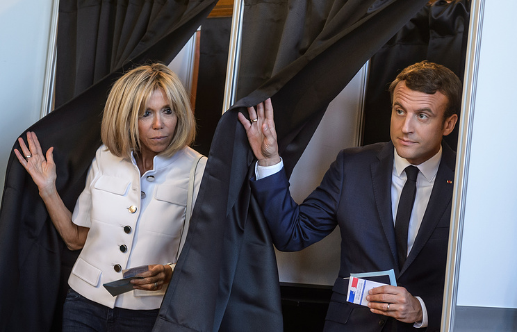 French President Emmanuel Macron with his wife Brigitte Trogneux cast their ballot at their polling station in the first round of the French legislatives elections in Le Touquet, France