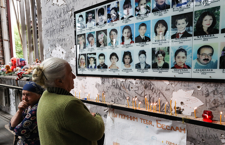 A woman looks at photos of the victims of the 2004 Beslan school siege
