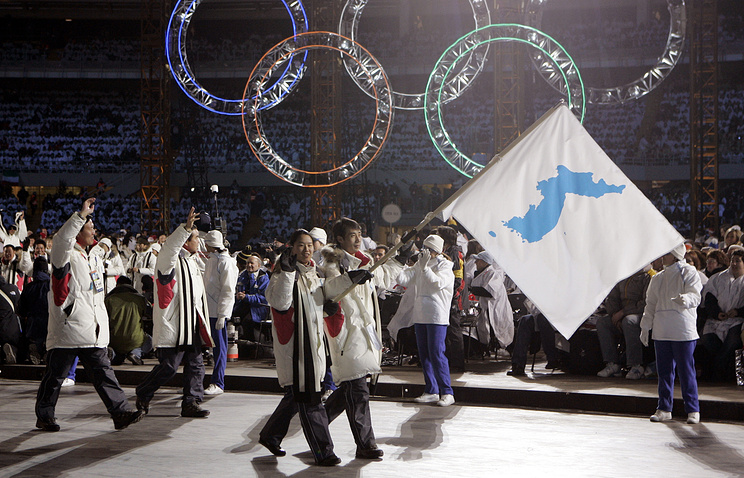 Korea flag-bearer', carrying a unification flag lead their teams during the 2006 Winter Olympics