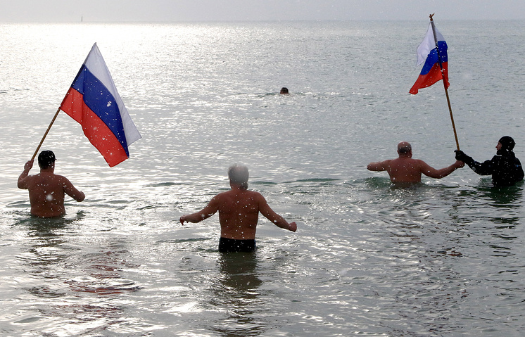 Crimean residents bath in the Black Sea holding Russian national flags (archive)
